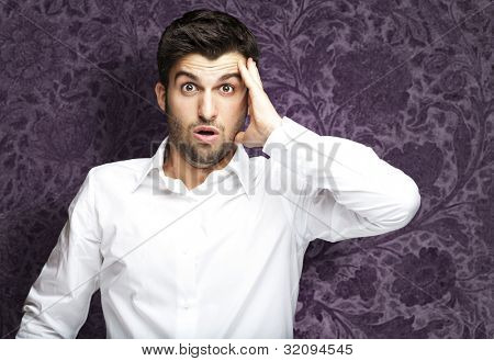 portrait of a young man surprised against a vintage wall