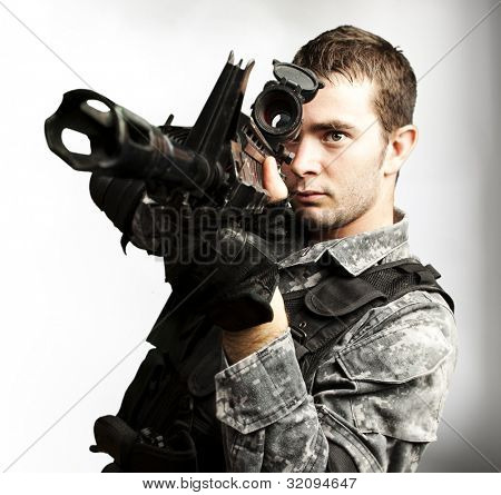 portrait of a young soldier aiming with a rifle over a black background