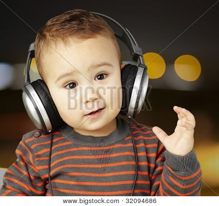 portrait of an adorable kid with headphones listening to music at a city by night