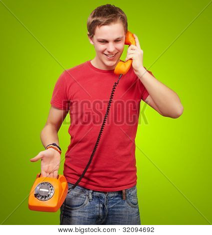 portrait of a young man talking on a vintage telephone over a green background