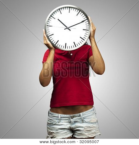 woman holding a clock in front of her head against a grey background