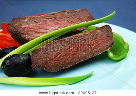 meat food : roasted fillet mignon on blue plate with pepper tomatoes and black greek olives over blue wooden table