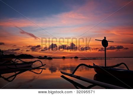 sunset over traditional fishing boats on Bali