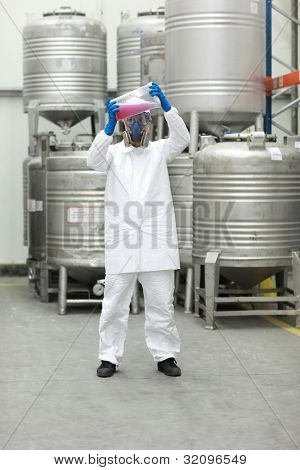 Specialist in protective uniform, mask, goggles, gloves examining liquid in plastic container