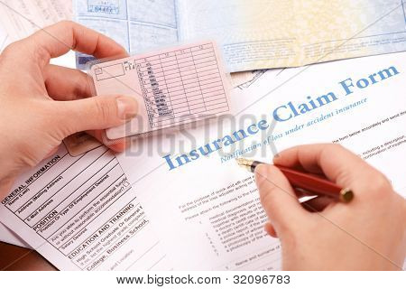 Hand filling in insurance claim form. Other papers like ID or vehicle documents in the background