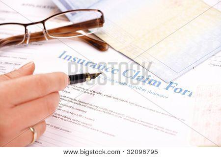 Mano rellenando el formulario de reclamo de seguro. Otros papeles como documentos de identificación o vehículo y vasos en el ba