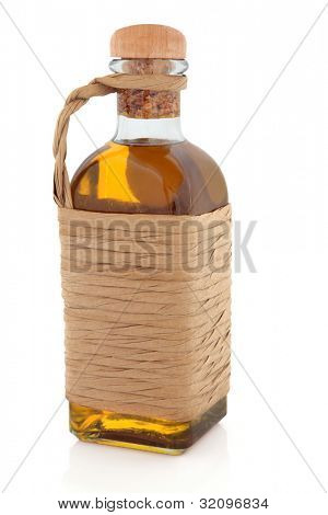 Olive oil in a traditional raffia style glass bottle on white background.