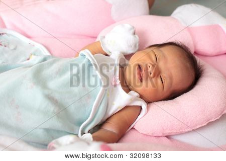 face of infant on baby bed