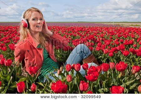 Portrait of a beautiful blond Dutch girl listening to music in tulips field
