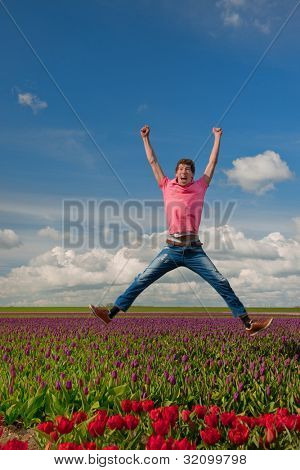 Young man is jumping above the typical dutch tulips