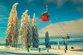 Picturesque Snow Covered Trees And Winter Ski Resort With Colorful Fast Cable Cars. Skiers On The Sk poster