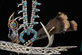 image of cultural artifacts  - Beautifully handcrafted silver and turquoise Native American squash blossom hanging with religious and spiritual artifacts as background - JPG