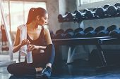 Fit Young Woman Sitting And Resting After Workout Or Exercise In Fitness Gym. Woman At Gym Taking A  poster