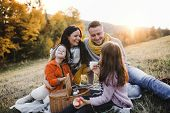 A Young Family With Two Small Children Having Picnic In Autumn Nature At Sunset. poster
