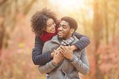 Happy Afro Couple In Love Walking In Autumn Park. Woman Hugging Man From Back poster