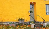 Yellow Brick House Entrance With Seasonal Wreath On Door And Porch Window On Autumn Day With Fall Le poster