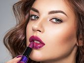 Young beautiful girl paints lips with purple  lipstick.  Young caucasian girl doing makeup. Model. C poster