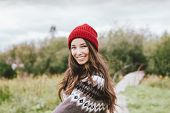 Beautiful Carefree Long Hair Asian Girl In The Red Hat And Knitted Nordic Sweater In Autumn poster