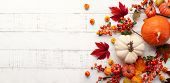 Festive autumn decor from pumpkins, berries and leaves on a white  wooden background. Concept of Tha poster