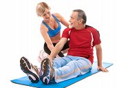stock photo of personal trainer  - Senior man doing fitness exercise with help of trainer at sport gym - JPG