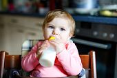 Cute Adorable Baby Girl Holding Nursing Bottle And Drinking Formula Milk. First Food For Babies. New poster