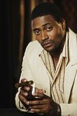 image of risque  - Portrait of African man holding drink and cigar - JPG