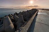 North Pier With Breakwaters, Sunset Seascape. Tetrapods Along Edges Of Pier. Beautiful Evening Seasc poster