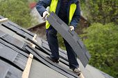Qualified Collar Worker Or Roofer In Protective Uniform Installing Asphalt Or Bitumen Tile On Top Of poster