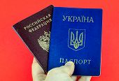 Two National Internal Passports, Red Russian Passport And Blue Ukrainian Passport Holding By Hand On poster