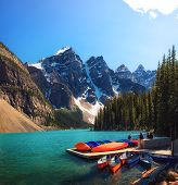 Canoes On A Jetty At Moraine Lake In Banff National Park, Alberta, Canada, With Snow-covered Peaks O poster