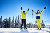 Smiling Couple Of Skiers In Goggles With Reflection, Posing On Skis With Ski Poles In Hands Up On Sn poster