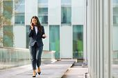 Happy Cheerful Latin Businesswoman Talking On Phone While Walking Outdoors. Young Woman In Office Su poster
