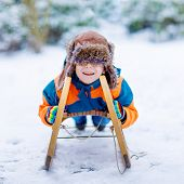 Little School Boy Having Fun With Sleigh Ride During Snowfall. Hapy Child Sledding On Snow. Preschoo poster