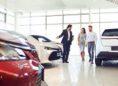 Couple And The Dealer Selling Cars Look The Car In The Showroom. poster