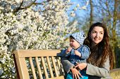 Toddler With Mom On The Background Of Flowering Trees. Little Baby On Hands Of Mother. Woman Playing poster