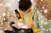 childhood, christmas and people concept - happy boy reading book with torch light in kids tent or te poster