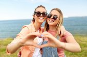 leisure and friendship concept - happy smiling teenage girls or best friends in sunglasses at seasid poster