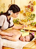 stock photo of ear candle  - Woman getting massage with ear candle in bamboo spa - JPG