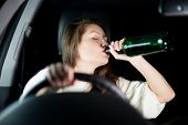Young Woman Drives A Car At Night And Drinks Alcohol While Driving, Not Looking At The Road. Dangero poster