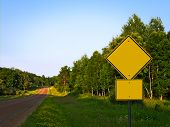 Yellow Warning Road Signs On Gravel Rural Country Roadside At Dusk - Add Your Text poster