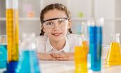 Soft Focus Of Inventive Girl In Protective Glasses Making Experiment With Chemicals In Flasks In Lab poster