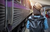 Young Asian Woman Traveler With Backpack In The Railway, Backpack And Hat At The Train Station With  poster