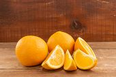 Oranges Lie On A Wooden Table. One Orange Is Cut Into Slices. poster