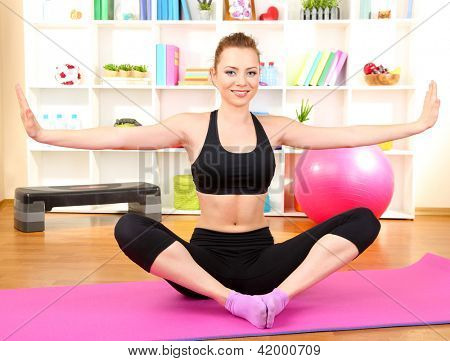 Young woman doing fitness exercises at home
