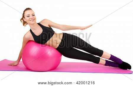 Young woman doing fitness exercises with gym ball isolated on white
