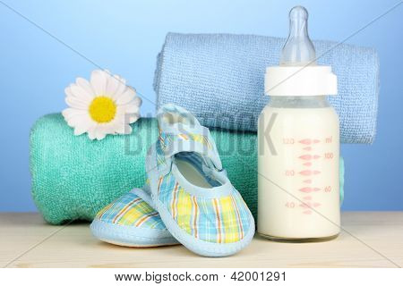 Baby bottle of milk with baby's bootees near towels on blue background