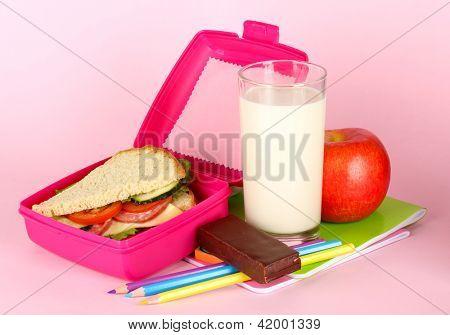Caixa de almoço com sanduíche, maçã, leite e artigos de papelaria em fundo rosa