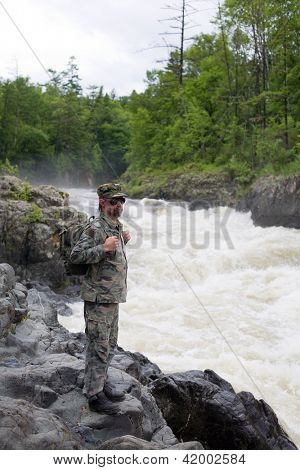 Backpacker standing on the shore of a mountain river. Russia. Primorskiy kray.