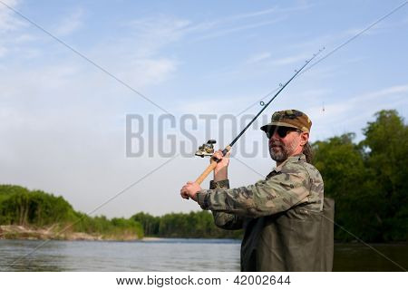 Fisherman makes casting tackle in the river.