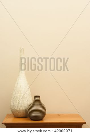 Tall White Vase And Short Striped Vase On Table